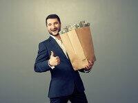 איש עומד עם שקית נייר מלאה בכסף לנזקקים