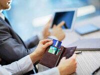 אישה משתמשת בכרטיסי האשראי שלה לשלם על הקניה