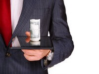 אדם מחזיק בידו טאבלט וכסף שהתקבל מהלוואה
