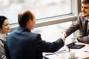 קבלן מקבל הלוואה ולוחץ ידיים ליועץ חוץ בנקאי
