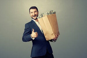 עובד מחזיק שק נייר עם כסף ומחייך